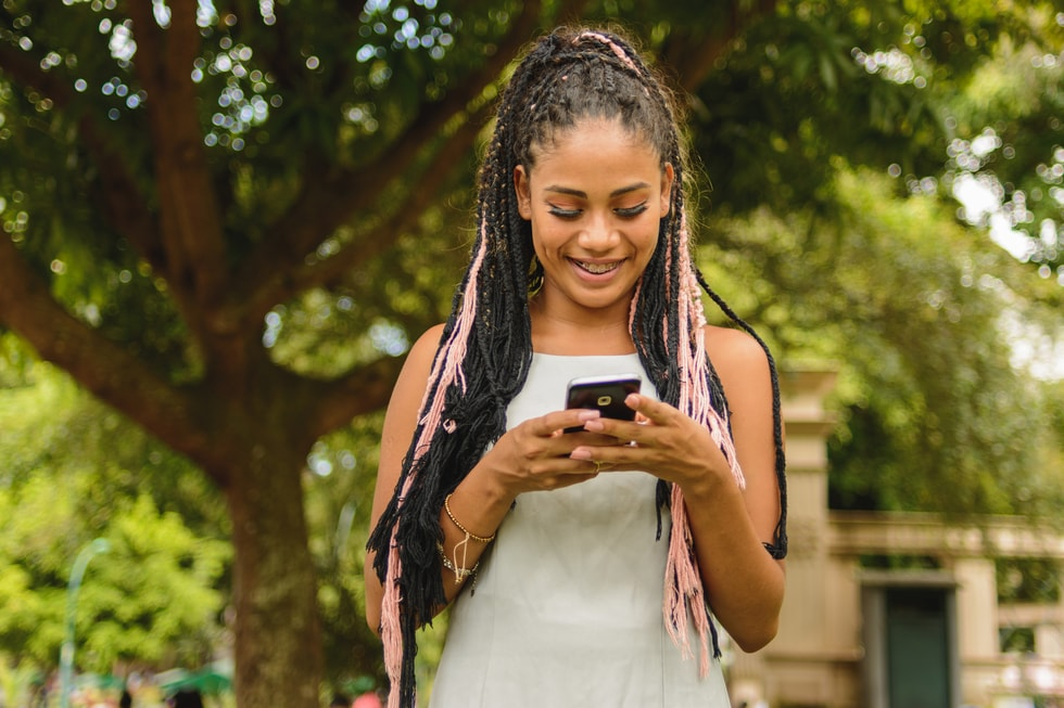 Girl holding mobile phone and smiling